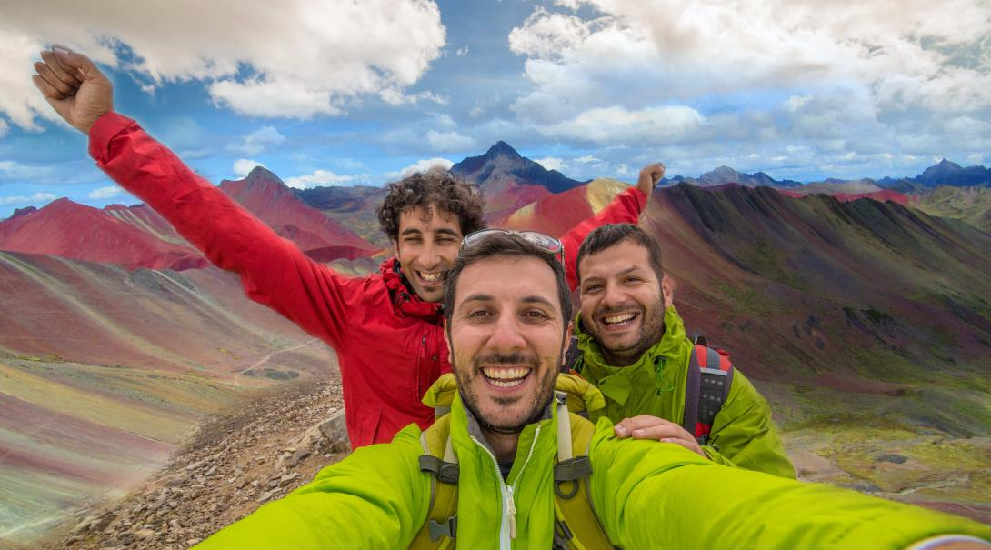 Travellers take a selfie with the Rainbow Mountains of Peru in the background.
